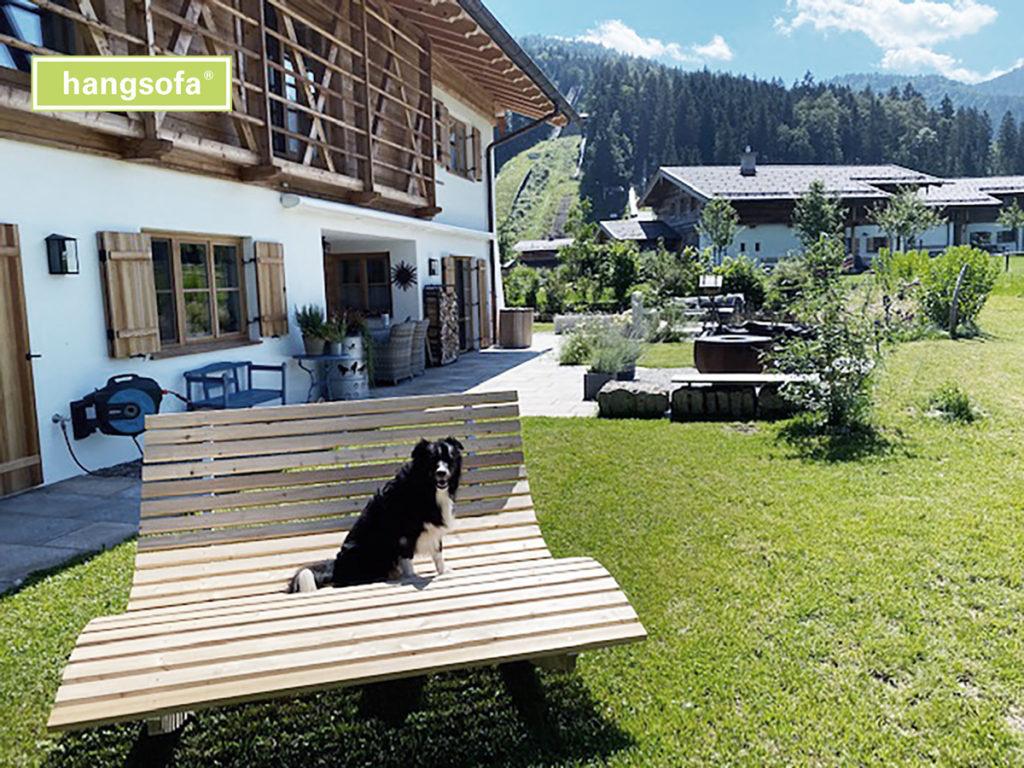 Hund sitzt auf Gartenliege im Garten