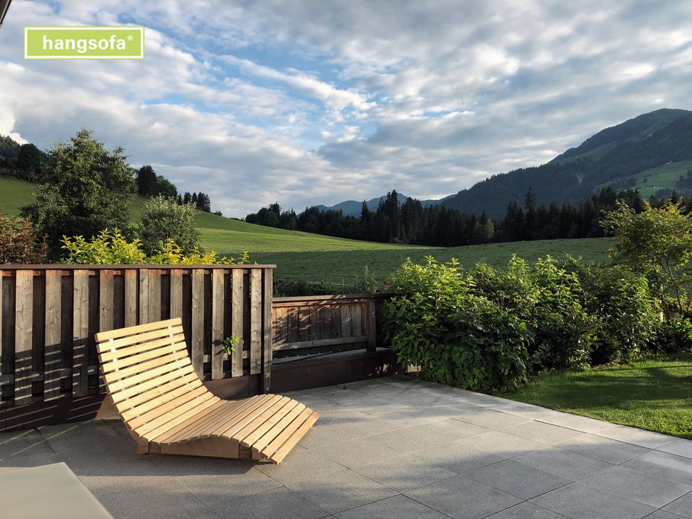 Relaxliege auf der Terrasse vor den Bergen