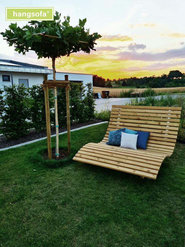 Gartenliege im Garten mit Sonnenuntergang