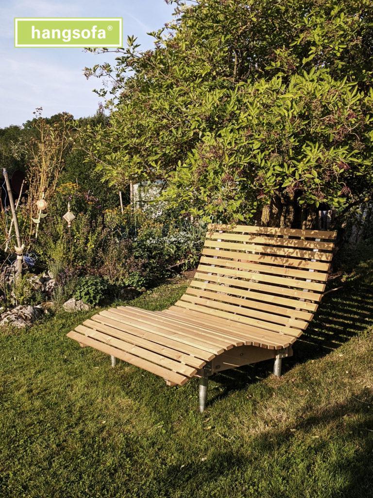 Hangsofa im schrägen Gartenhang bei Sonnenschein unter einem Baum