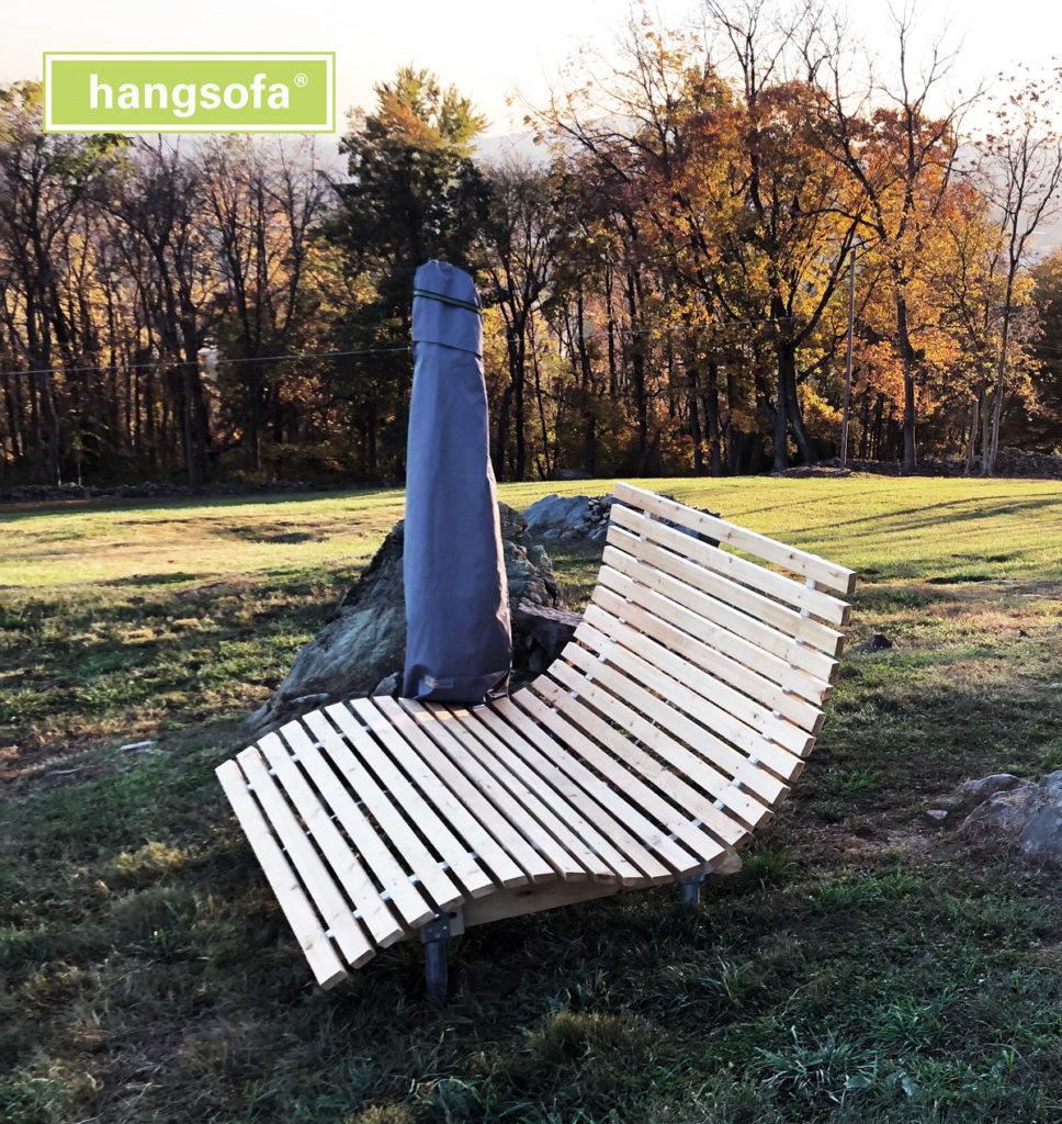 Relaxliege im Rasen mit Sonnenschirm bei Sonnenaufgang