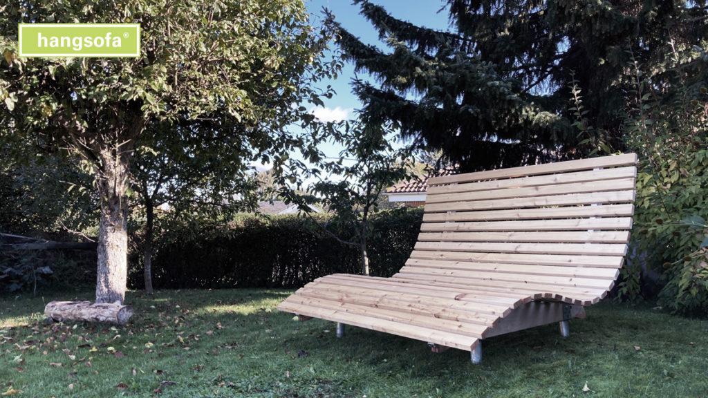Geschwungene Gartenliege aus Holz mit Lärche im schönen Garten