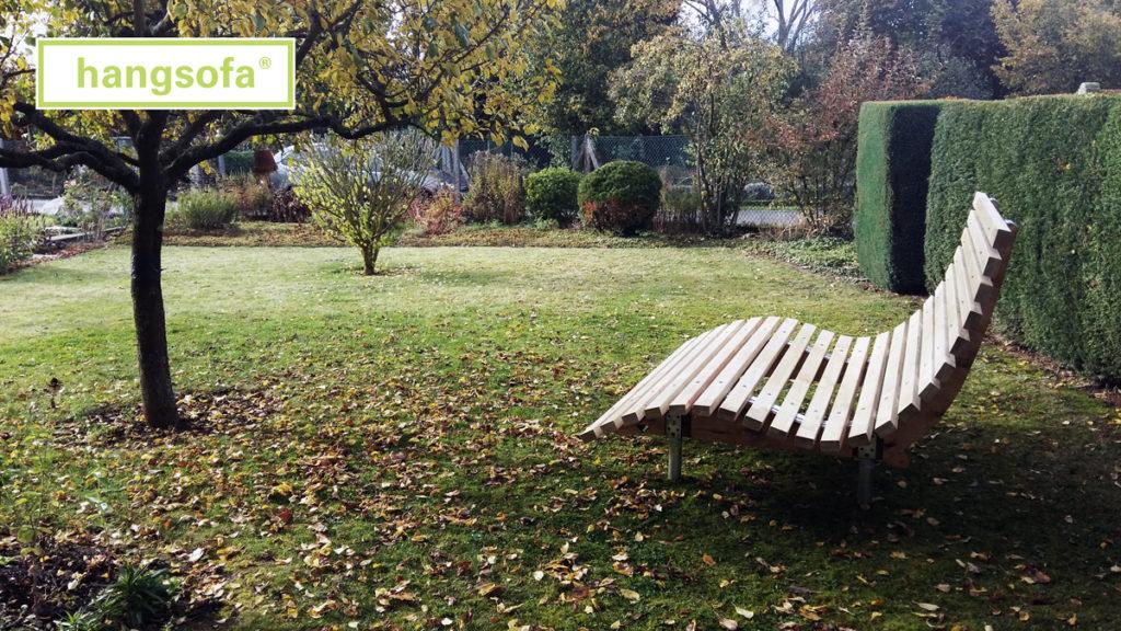 Große Gartenliege im Herbst in schönem Garten