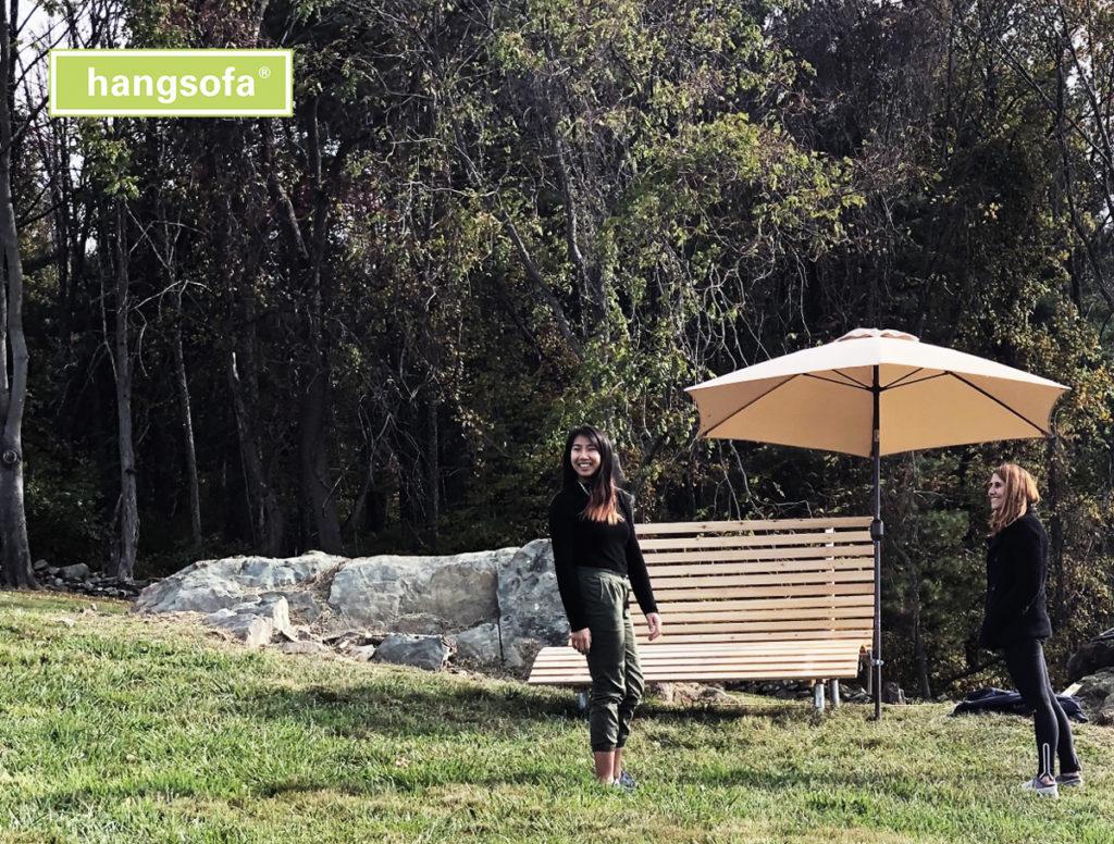 Relaxliege mit Sonnenschirm im Rasen mit zwei Frauen davor