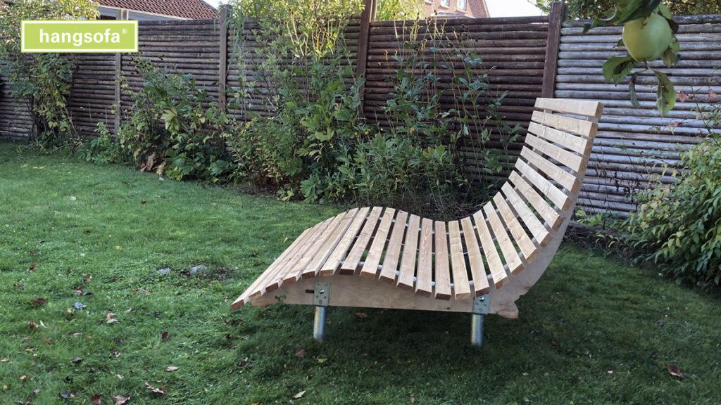 Geschwungene Relaxliege aus Lärche und mit Erdschrauben im Garten
