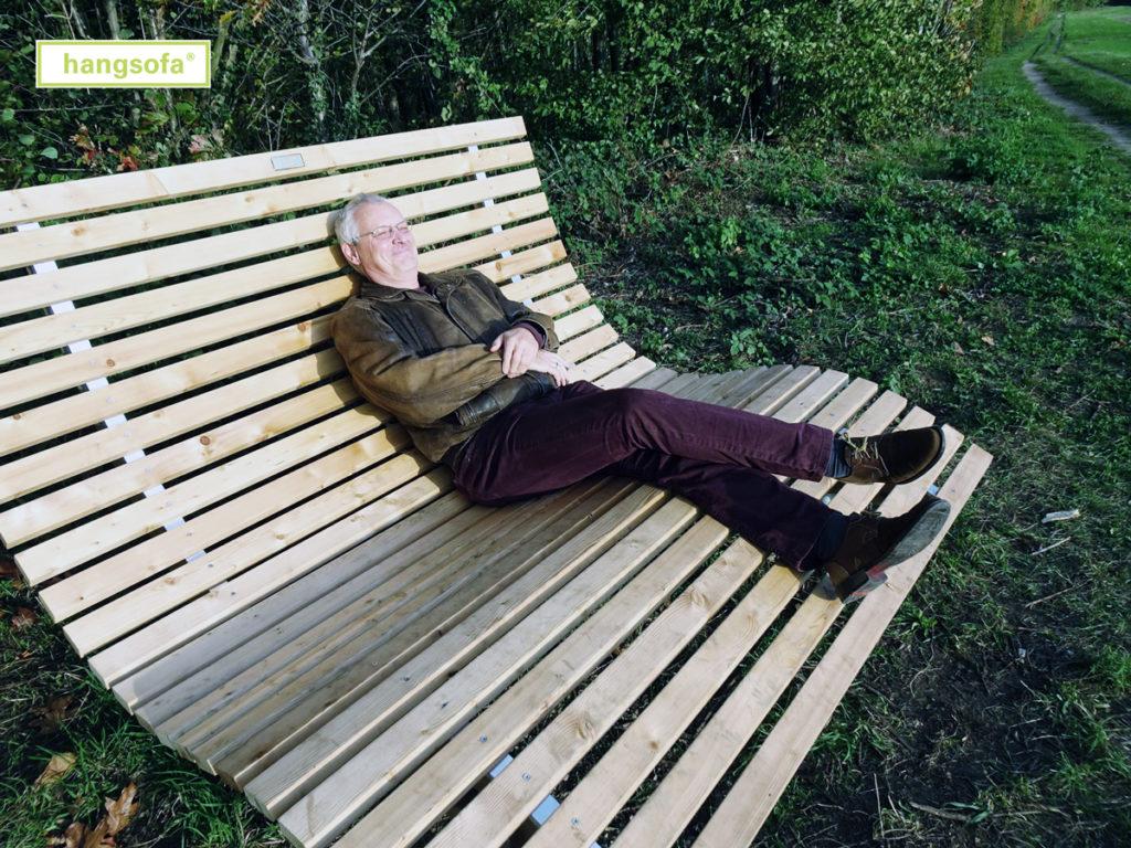 Relaxliege aus Holz mit Mann mit Lederjacke neben Feldweg