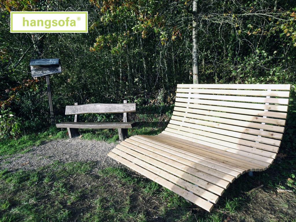 Relaxliege aus Holz mit Bodenhuelsen auf Wanderweg