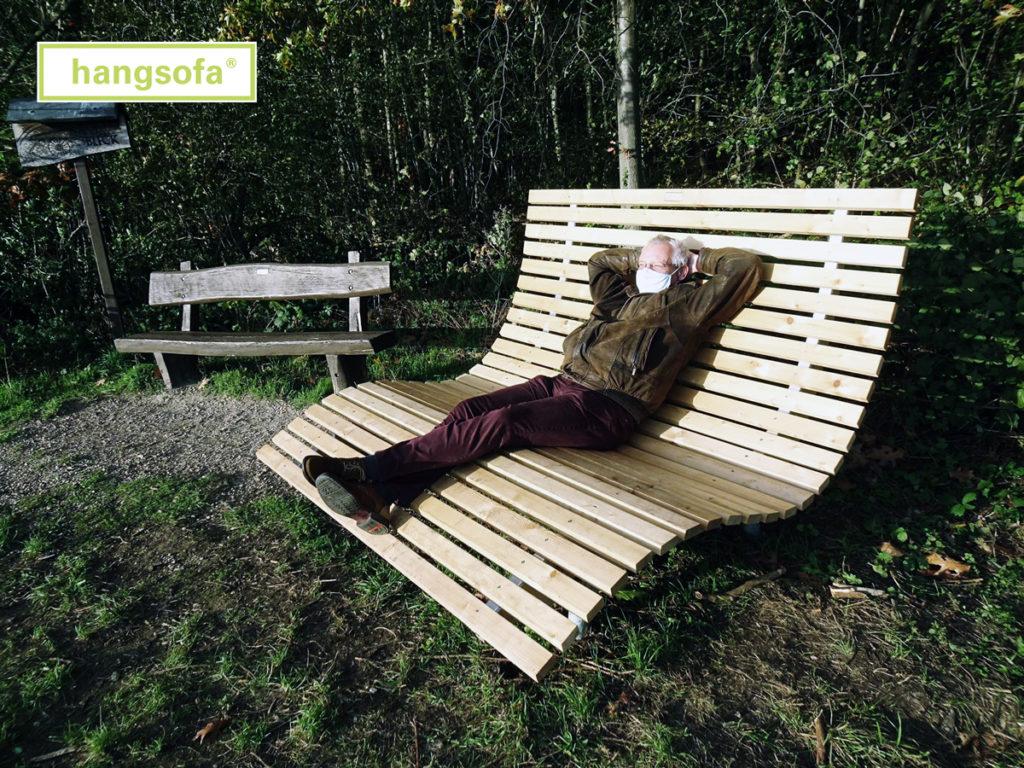 Relaxliege aus Lärchenholz mit Wanderer im Sonnenschein