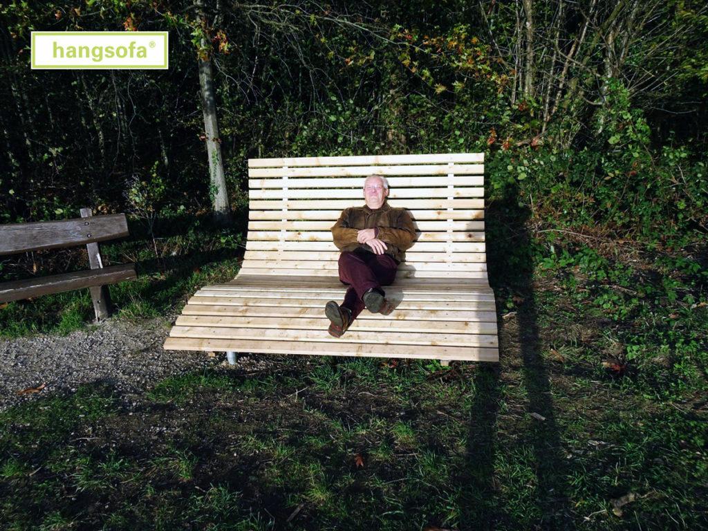 Mann liegt auf Relaxliege aus Holz auf der Lichtung